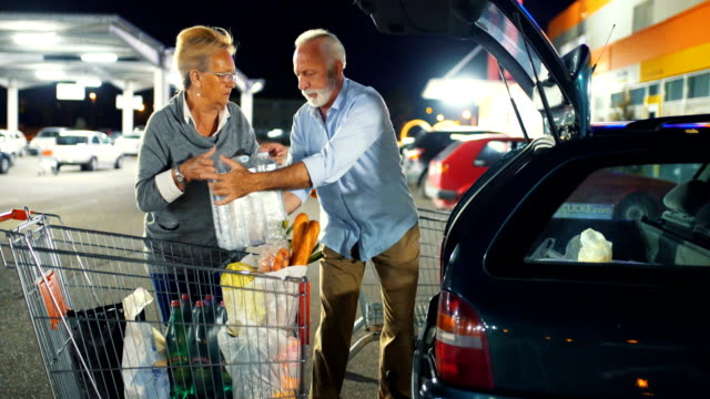 Senior couple packing groceries after shopping. Closeup side view of early 60's couple packing their groceries into their car at a big parking lot next to a supermarket. They are doing their shopping at night. 4k dolly shot. chores stock videos & royalty-free footage