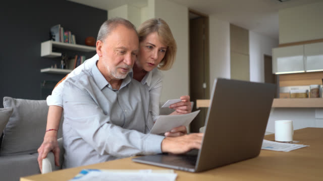 vídeos de stock e filmes b-roll de senior couple paying bills at home using a credit card and a laptop both smiling - bills couple