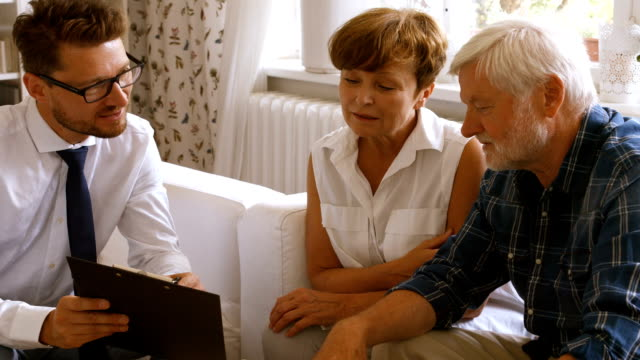 Senior couple planning their investments with financial advisor Senior couple planning their investments with financial advisor at home guidance stock videos & royalty-free footage