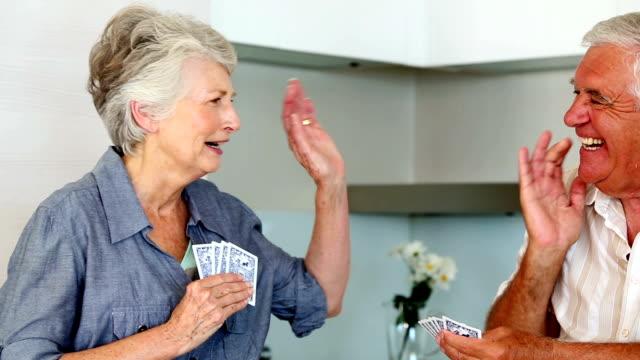 coppia senior giocare a carte al banco - 60 69 anni video stock e b–roll