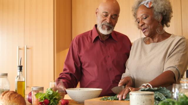 vídeos de stock, filmes e b-roll de pares sênior que preparam o brunch junto na cozinha - vegetarian meal