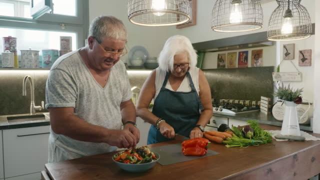 Senior Couple Preparing Salad in Family Kitchen