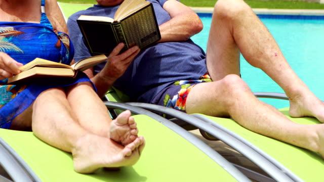 äldre par läsa böcker på solstol - sarong bildbanksvideor och videomaterial från bakom kulisserna