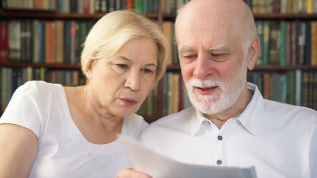 Senior couple reading investment financial documents. Family of retired pensioners with tax report Senior couple in white t-shirts at home with investment financial documents. Family of retired pensioners reading tax report. Bookcase bookshelves in background mortgages and loans stock videos & royalty-free footage