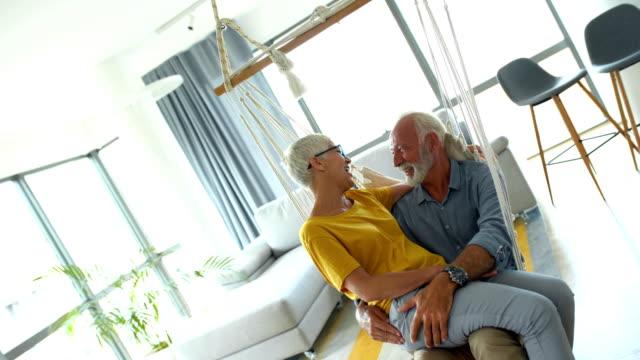 senior couple relaxing in a rocking swing - siwe włosy filmów i materiałów b-roll