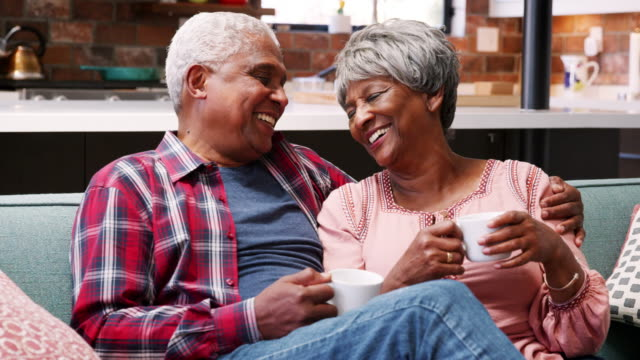 Senior couple relaxing on sofa at home with hot drink and chatting - shot in slow motion