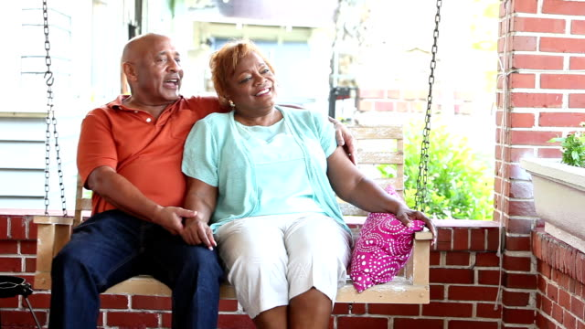 senior couple relaxing, talking on porch swing - portico video stock e b–roll