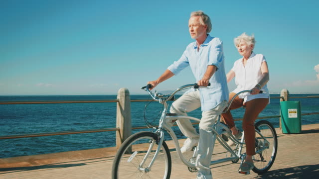 Senior couple riding tandem bicycle against sky
