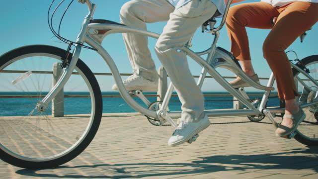 Senior couple riding tandem bicycle on promenade