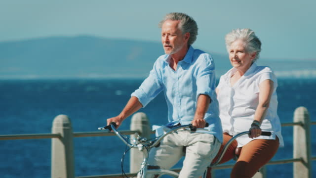 Senior couple riding tandem bicycle on sunny day