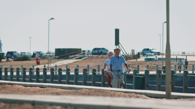 Senior couple riding tandem bike in summer