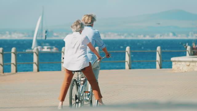 Älteres Paar Reiten Tandem Fahrrad auf promenade – Video
