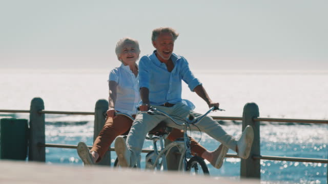 Senior couple riding tandem bike on promenade Dolly shot of senior couple riding tandem bike with legs apart. Elderly male and female are on promenade. They are enjoying summer vacation. healthy lifestyle stock videos & royalty-free footage