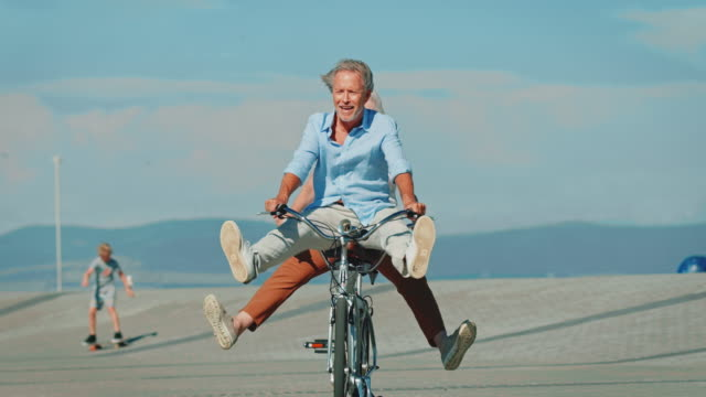 senior couple riding tandem bike with legs apart - giovane nell'animo video stock e b–roll