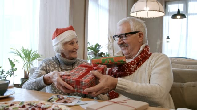 Senior Couple Sharing Christmas Gifts at Restaurant Table video