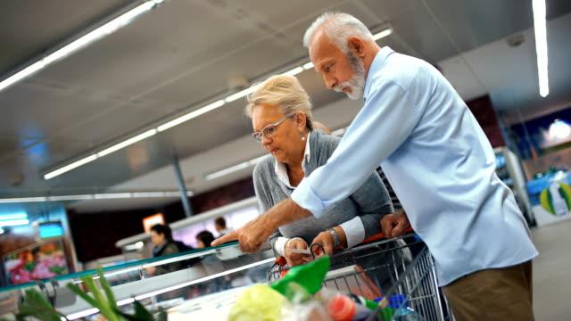 senior couple shopping in supermarket. - замороженные продукты стоковые видео и кадры b-roll
