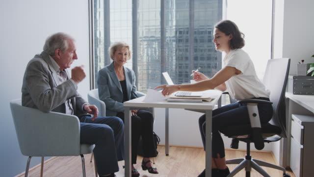 senior couple signing document in meeting with female financial advisor in office - финансовый консультант стоковые видео и кадры b-roll