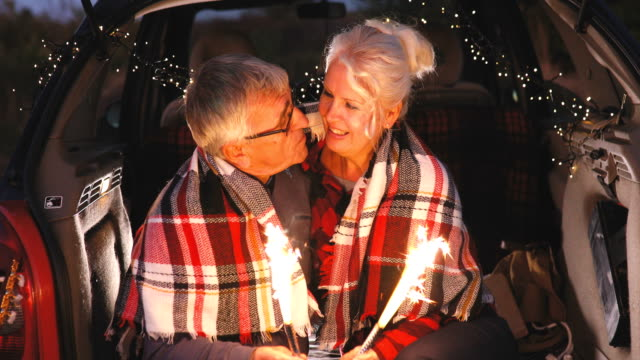 Senior couple sit in open car trunk and hold spark sticks in their hands Senior couple sit in open car trunk and hold spark sticks in their hands christmas fun stock videos & royalty-free footage