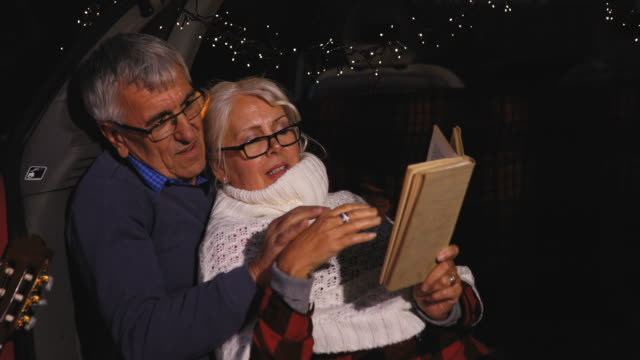 Senior couple sit in open car trunk and reading a book video