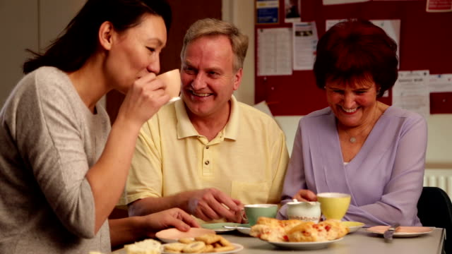 starszy para usiąść z młodego lady, rozmawiając na herbatę - scone filmów i materiałów b-roll