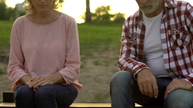 senior couple sitting apart on bench outdoors, deception, breakup and resentment - communication problems stock videos & royalty-free footage