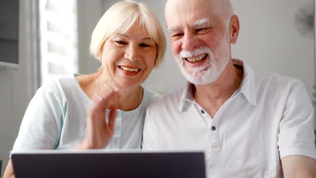 Senior couple sitting at home talking via messenger app Skype. Smiling waving hands in greeting video