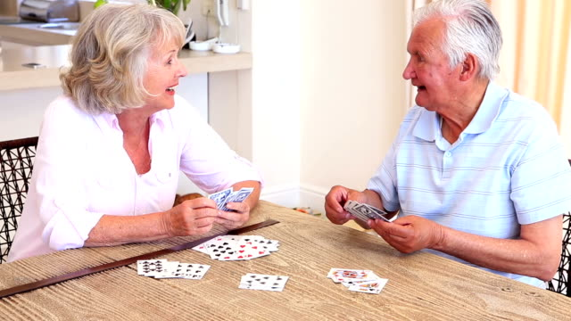 Senior couple sitting at table playing cards video