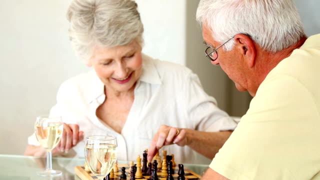 senior coppia seduta al tavolo di gioco di scacchi - 60 69 anni video stock e b–roll