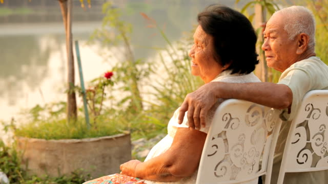 Senior couple sitting near river during sunset影片