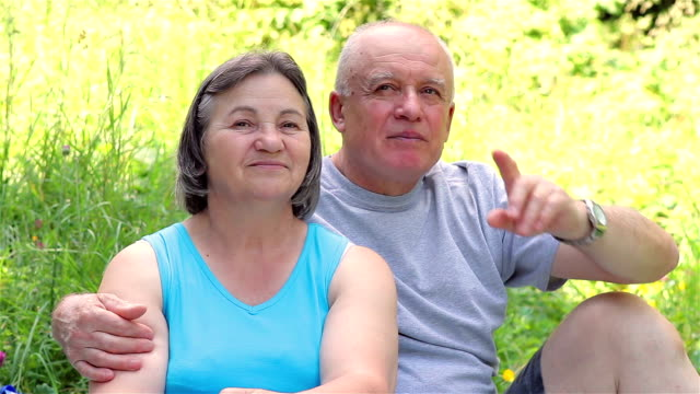 Senior couple sitting on grass together relaxing video