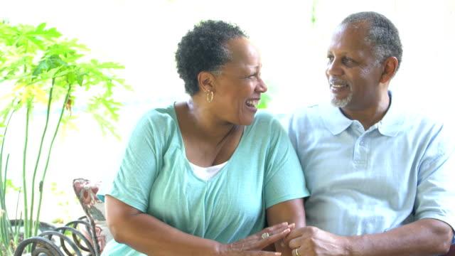 senior couple sitting on patio, conversing - 60 69 anni video stock e b–roll