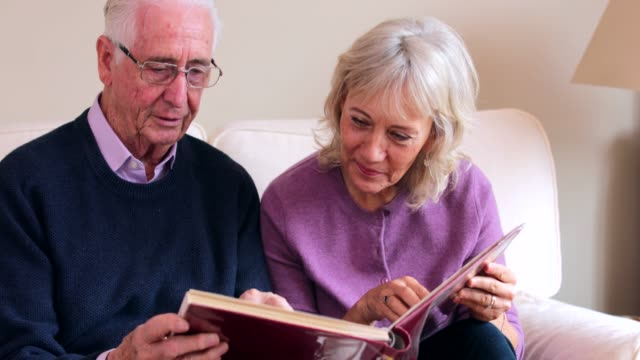senior couple sitting on sofa and looking at photo album together - uomo nostalgia video stock e b–roll