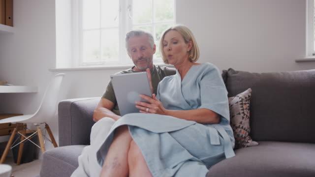 stockvideo's en b-roll-footage met senior paar zittend op de bank thuis met behulp van digitale tablet samen - een tablet gebruiken