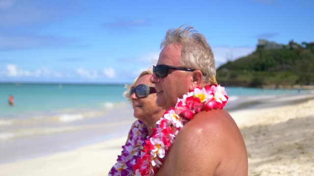 Senior couple sitting on the beach on Hawaii island in 4K Slow motion 60fps video