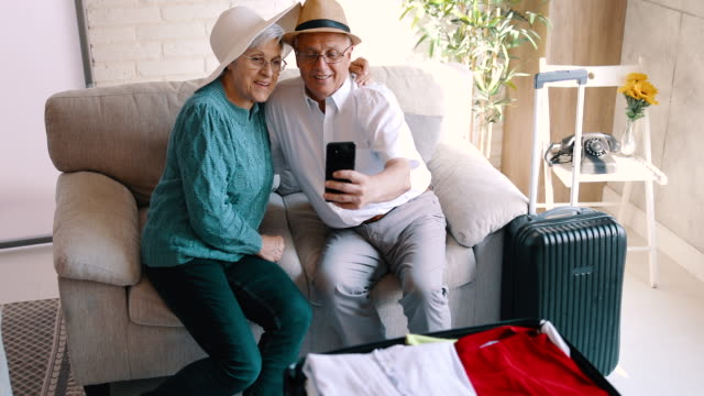 Senior couple sitting on the sofa and taking a selfie Senior couple sitting on the sofa and taking a selfie anticipation stock videos & royalty-free footage
