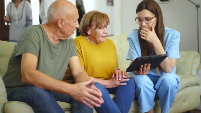 Senior couple sitting on the sofa and talking with nurse video