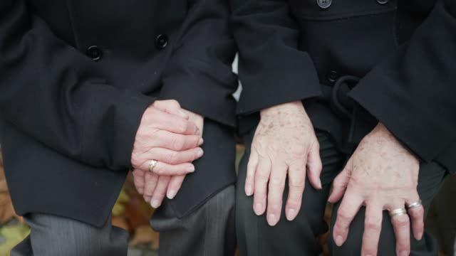 a senior couple sitting together holding each others hands - true love angielski zwrot filmów i materiałów b-roll