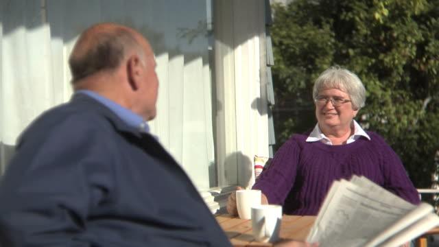 anziana coppia seduta insieme sul porch - portico video stock e b–roll