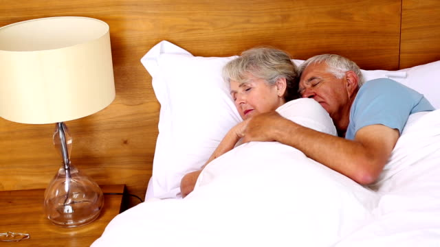 Senior couple sleeping in bed video