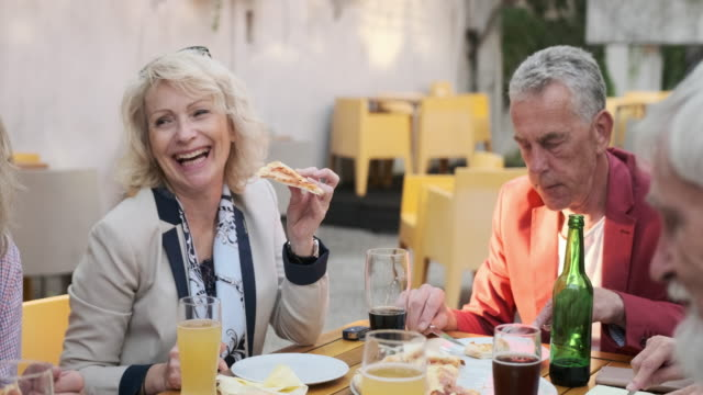Senior Couple Smiling at Each Other Over Drinks and Pizza video