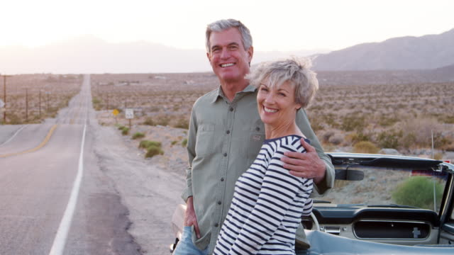Senior couple standing by car smiling to camera, close up