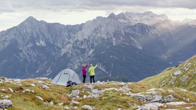 ds senior par stående bredvid sitt tält på ett högt berg äng och talar om vyn - bergsrygg bildbanksvideor och videomaterial från bakom kulisserna