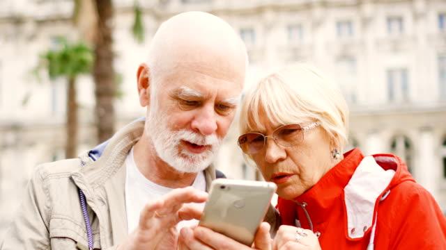 vidéos et rushes de couple de personnes âgées se tenant en rue de parcourir dans smartphone. étudier la ville carte app sur téléphone mobile - carte france
