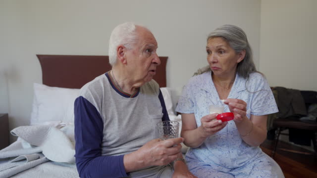 Senior couple Taking medicine together