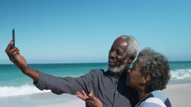 senior-paar beim fotografieren am strand - aktiver senior stock-videos und b-roll-filmmaterial