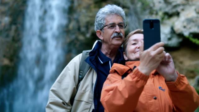 滝で年配のカップル撮影 selfie - 老夫婦点の映像素材/bロール