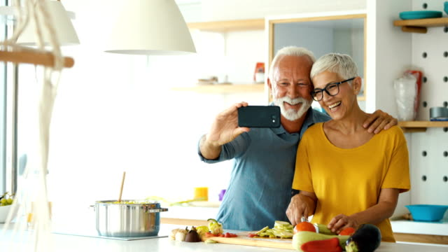 senior couple taking selfies at home. - capelli grigi video stock e b–roll