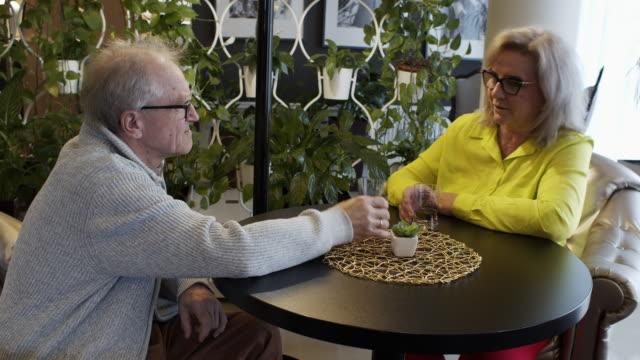 senior couple talking and drinking in hotel lobby. - abiti pesanti video stock e b–roll