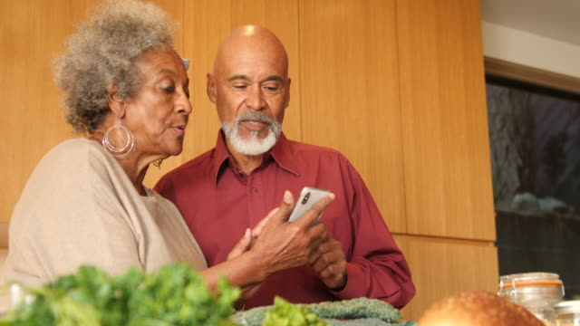 Senior couple talking over mobile phone in kitchen