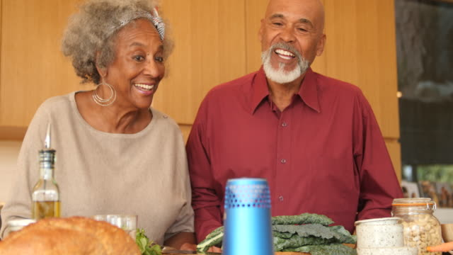 vídeos de stock, filmes e b-roll de pares sênior que falam ao altofalante na cozinha em casa - vegetarian meal